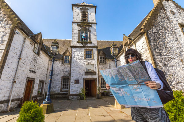 Young woman tourist looks at the map of Scotland. In the background Cowane's Hospital, a historic building, in Stirling town, Central Scotland, UK, Europe Copyright Benny Marty