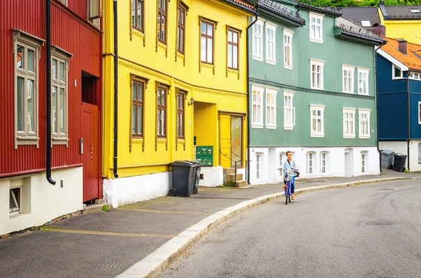 Colorful wooden house architecture and a young tourist on a bike in Oslo, Scandinavia Copyright Anna Jedynak
