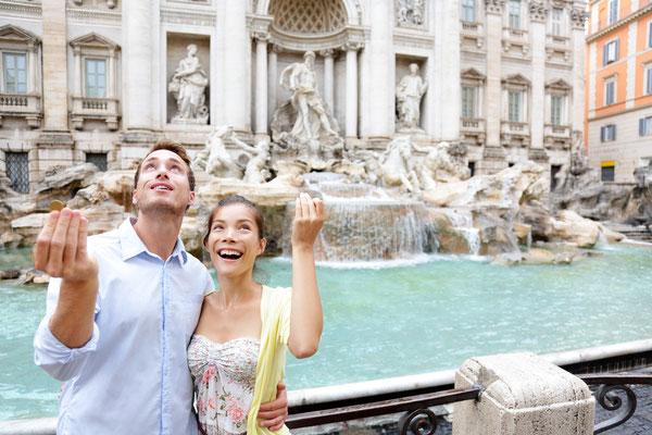 Travel couple trowing coin at Trevi Fountain, Rome, Italy - Copyright Maridav