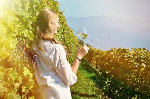 Girl tasting white wine among vineyards. Lavaux, Switzerland Copyright Capricorn Studio