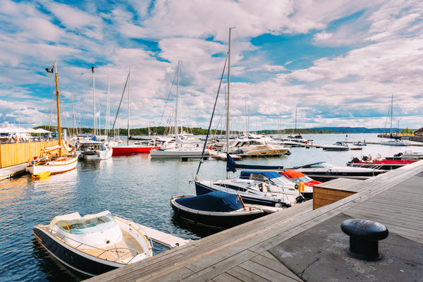 Yachts moored at town quay In Sunny Summer Day. District Aker Brygge in Oslo, Norway. Summer Evening Copyright Grisha Bruev