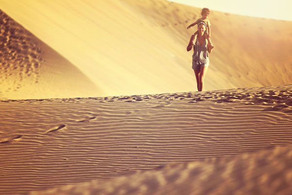 Gran Canaria - European Best Destinations - Fit mother with son walking in a desert in Gran Canaria, Maspalomas on the sunset Copyright SASHAandLENKA