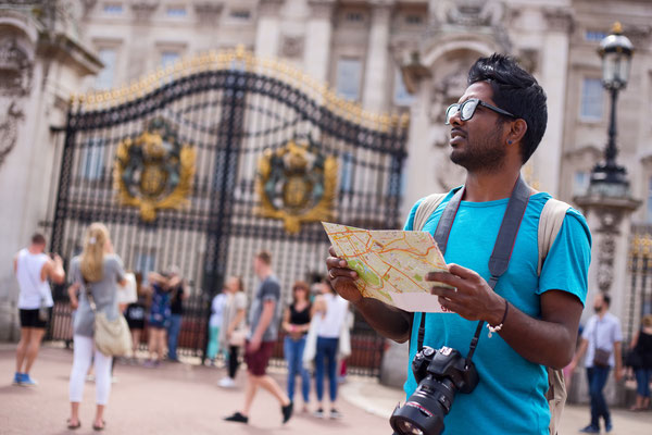 Indian tourist outside buckingham palace holding a map and his camera Copyright Michaelpuche