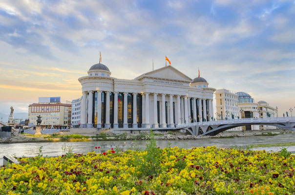 Amazing sunrise of archaeological museum of Macedonia with river Vardar, bright colorful sky and spring flowers foreground Copyright  zefart