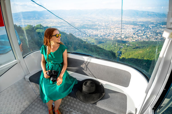 Young woman tourist sitting in cable car on the way to the top of Vodno mountain near Skopje city in Macedonia Copyright RossHelen