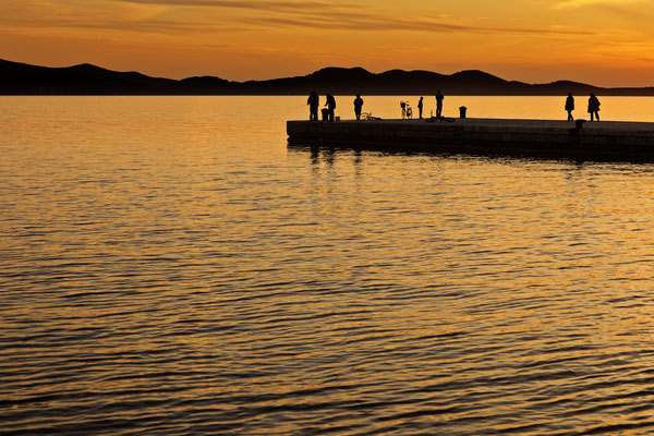 People standing on a jetty at sunset in Zadar, Dalmatia, Croatia - Copyright Ppictures