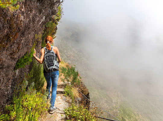 Young woman walking in the path on the mountain edge, Portugal, Madeira Copyright Nomad_Soul