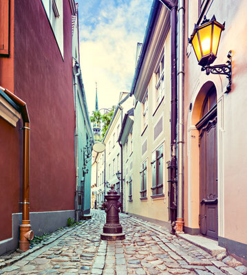 Narrow street in old city of Riga at night. Image toned in vintage warm colors for inspiration of retro style effect Copyright Sergei25