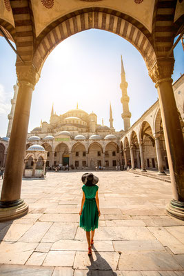 Young woman traveler in the green dress and hat walking to the Blue Mosque in Istanbul - Copyright RossHelen