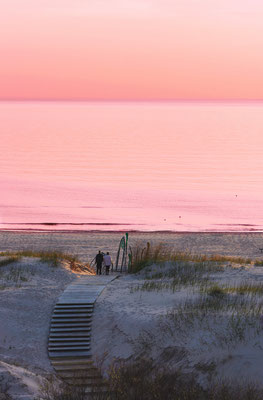 Couple at the beach at sunset in Ventspils, the Baltic Sea by Roman Babakin