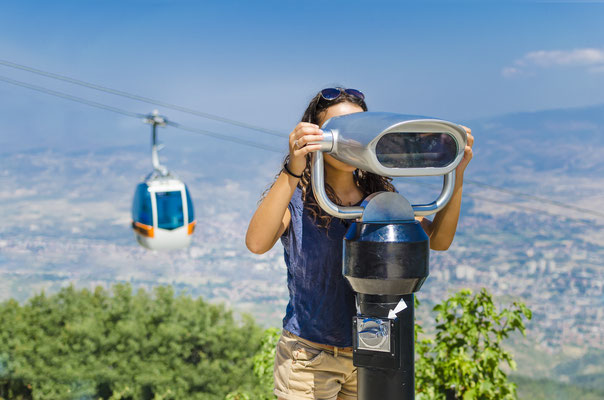 Great Spectators - Stock Image. Beautiful girl is looking at coin operated binocular at the top of Vodno mountain, Skopje, Macedonia with cable car at background Copyright zefart