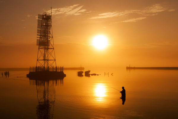 Fisherman in the water near lighthouse on the outstanding sunset background with reflection on foggy weather on Baltic sea - Copyright Konstantin Romanov