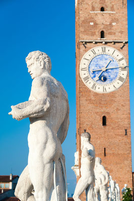 Statues on the top of the Basilica palladiana, the main monument of the town Vicenza and the clock tower copyright Marco Ossino