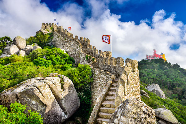 Sintra, Portugal at Castle of the Moors wall with Pena National Palace in the distance - Copyright Sean Pavone