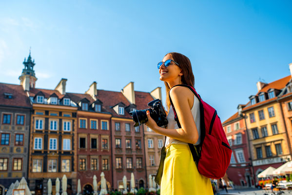 Female young traveler with backpack and photocamera in the old town market square in Warsaw, Poland Copyright RossHelen