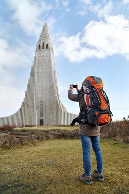 rear view of backpacker tourist travel woman taking pictures of the Hallgrimskirkja cathedral in reykjavik iceland Copyright Daxiao Productions