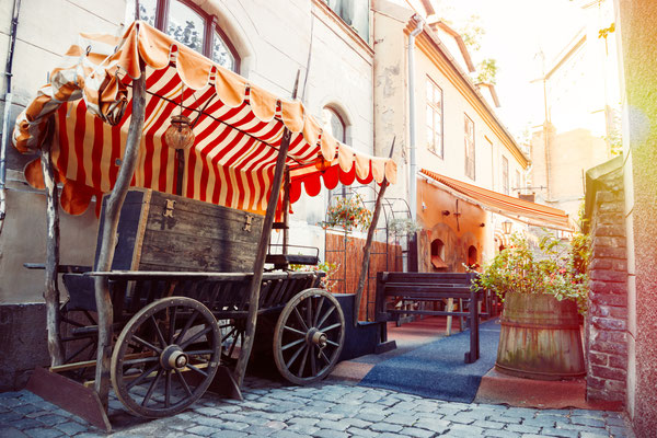 Medieval street and fragment of outdoors cafe in the old city of Riga, Latvia Copyright Chamille White