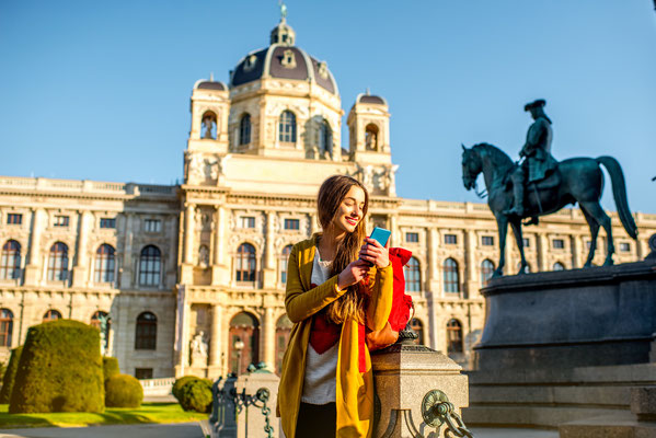 Young female tourist with smart phone on Maria Theresa square near museum of Natural history in Vienna. Copyright Ross Helen