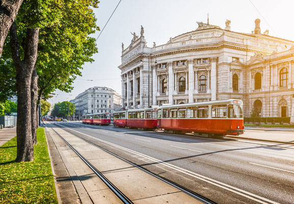 Famous Wiener Ringstrasse with historic Burgtheater (Imperial Court Theatre) and traditional red electric tram Copyright canadastock