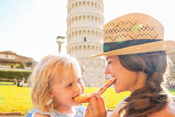 Happy mother and baby girl eating pizza in front of leaning tower of Pisa, Italy - Copyright Alliance