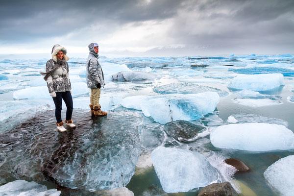 Tourists stand on the massive icebergs in lake Jokulsarlon in Iceland in winter Copyright Dennis van de Water