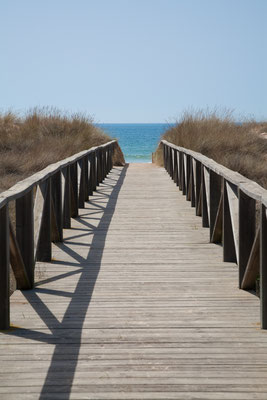 wooden walkway with hand rail with green blue turquoise water ocean or sea over nature in Vejer Palmar Beach seaside in Cadiz AndalusiaSpain copyright Quintanilla