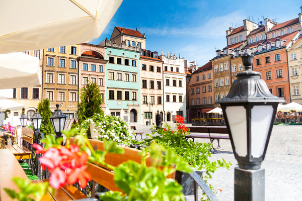 Warsaw old town marketplace square, street lamp in cafe and flowers on foreground copyright  Sergey Novikov