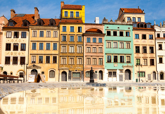 Reflecting surface of fountain and Warsaw, Poland old town marketplace square and colorful houses Copyright  Sergey Novikov