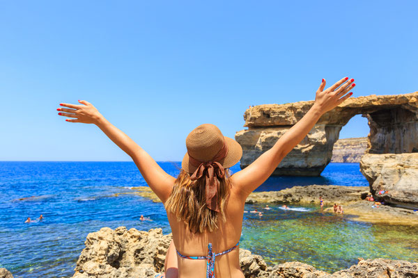 tourist wears hat, bikini, raises hands up and enjoys summertime with background of Azure window, famous tourist attraction on Gozo island, Mediterranean sea, Malta Copyright  Littleaom