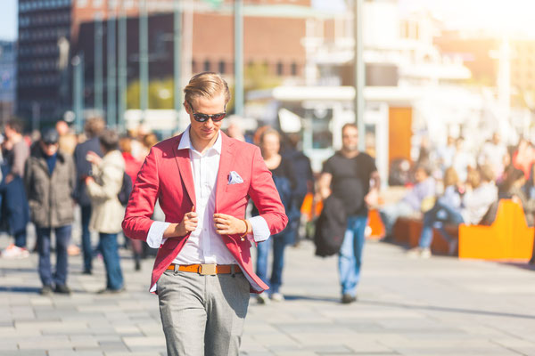 Fashioned young man in Oslo walking on crowded sidewalk with people on background. He has nordic facial features, and wearing a red jacket with gray trousers Copyright William Perugini