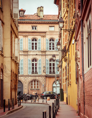 Narrow historic street with old buildings in Toulouse, France Copyright Tatyana Vyc