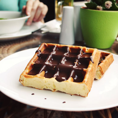 Viennese Waffles covered with chocolate. Aged photo. Vienna Waffles covered with chocolate topping. White plate with sweet food Copyright Lora Sutyagina