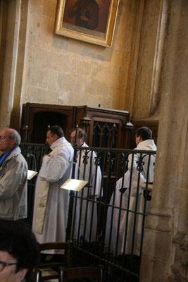Avant de concélébrer, les prêtres revêtent leur aube dans les chapelles latérales