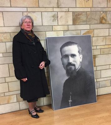 Gisèle Poignant pose à côté de la photo du P. Marcel Denis