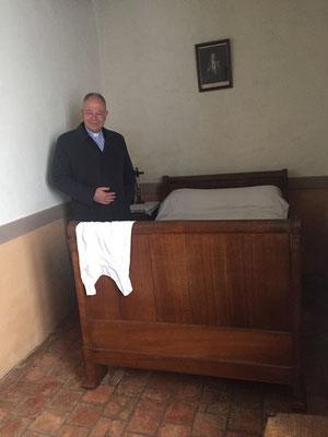 A côté du lit de Rose Taillé, le P. Olivier Ruffray, recteur du sanctuaire de Lisieux
