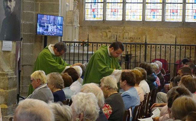 Les prêtres passent dans les rangs pour imposer les mains sur celles et ceux qui reçoivent le sacrement.