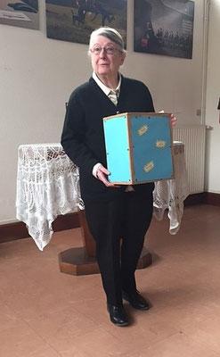 Tenant le tronc, l'ancienne présidente de la paroisse protestante Madame Anne Decaillon