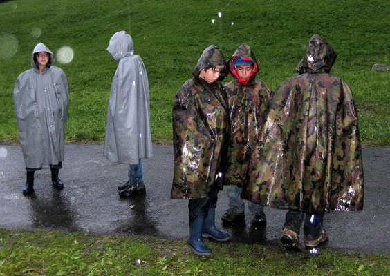 Die Kinder in den Pelerinen sind wenig beeindruckt vom starken Regen