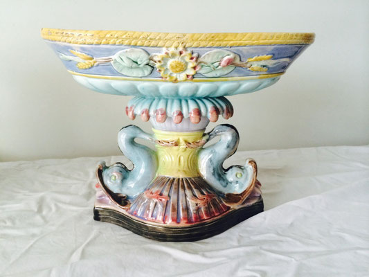 Majolica centrepieces floret pattern to dish resting on pedestal with two supporting dolphins