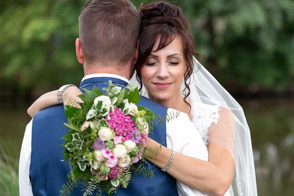 Braut umarmt Bräutigam