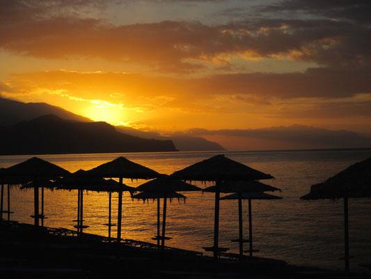 Sonnenschirme und Sonnenuntergang am Strand von Paleochora