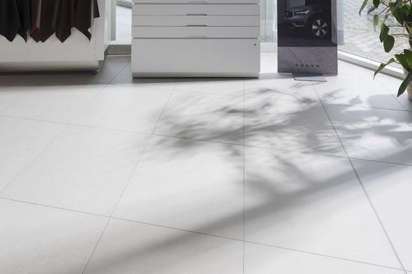 Raisch Fliesenfachgeschäft und hochwertige Fliesenarbeiten in der Region Stuttgart - hier: Volvo Autohaus Gölz Stuttgart - www.raisch-fliesen.de - italienische Feinsteinzeug Bodenfliesen im Verkaufsraum von Volvo Gölz. mit Schatten