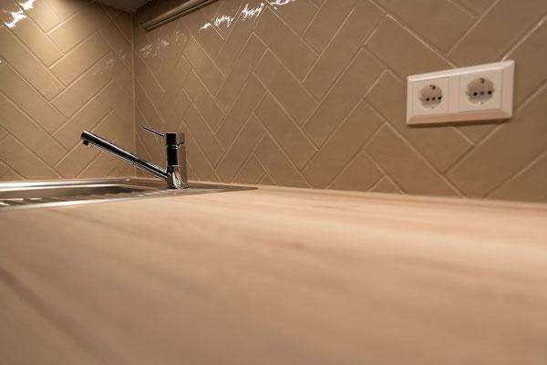 Raisch Fliesenfachgeschäft und hochwertige Fliesenarbeiten in der Region Stuttgart - Küchenrückwand Fischgrätmuster Riemchen Fliesen crème beige nude - www.raisch-fliesen.de - Ansicht schräg auf die Arbeitsplatte