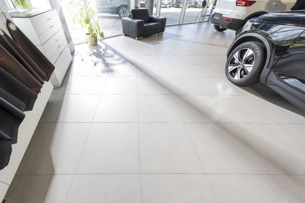 Raisch Fliesenfachgeschäft und hochwertige Fliesenarbeiten in der Region Stuttgart - hier: Volvo Autohaus Gölz Stuttgart - www.raisch-fliesen.de - italienische Feinsteinzeug Bodenfliesen im Verkaufsraum von Volvo Gölz. im Gegenlicht