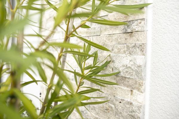 Raisch Fliesenfachgeschäft und hochwertige Fliesenarbeiten in der Region Stuttgart - hier: Außenwandgestaltung mit Natursteinen - www.raisch-fliesen.de - Ansicht mit Blumen