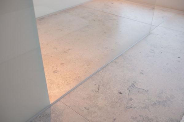 Fliesenlegerfachbetrieb Fliesenfachgeschäft Matthias Raisch - einzigartige Natursteinplatten aus Jura Marmor grau blau in erhabenem Stuttgarter Penthouse. Dusche mit Glaswand