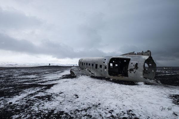 Flugzeugwrack am schwarzen Sandstrand