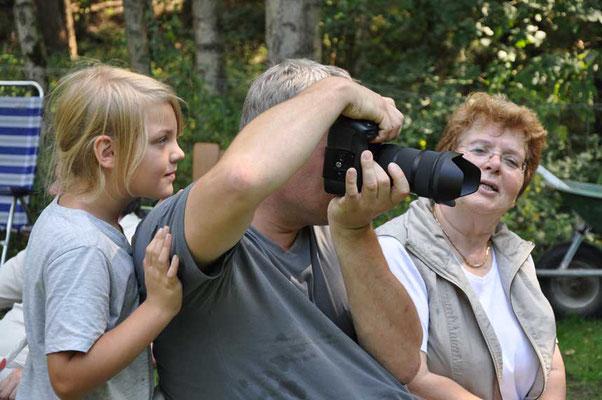Lara schaut ihrem Vater Jens Böse beim Fotografieren über die Schulter, Rosemarie Neuwardt schaut zu.