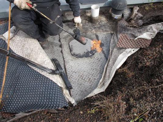 Reparatur einer Flachdachabdichtung aus Bitumenbahnen durch Verschweißen.