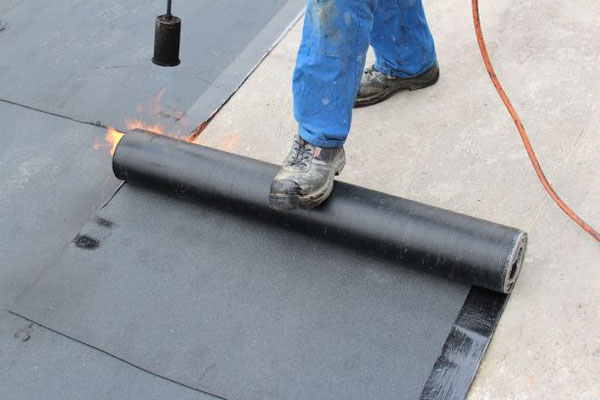 Herstellung einer Flachdachabdichtung aus Bitumenbahnen durch Verschweißen.